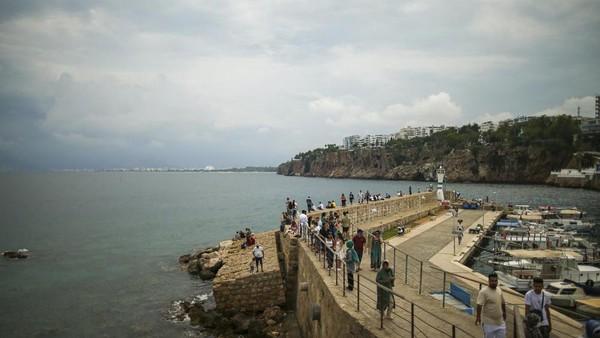 Pada hari yang sama turis berdatangan ke pelabuhan Tua di Antalya, (AP)