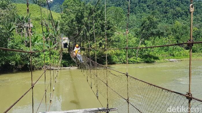 Warga Dusun Rantelalamun, Desa Pamoseang, Kecamatan Mambi, Kabupaten Mamasa, Sulbar melintasi jembatan rusak.