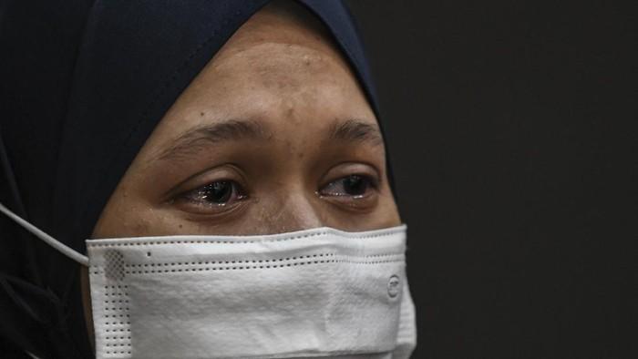 Seorang tenaga kesehatan meneteskan air mata saat melepas jenazah rekannya Liza Putri Noviana di Rumah Sakit Darurat COVID-19 (RSDC) Wisma Atlet Kemayoran, Jakarta, Kamis (24/6/2021). Liza merupakan tenaga kesehatan pertama di RSDC yang meninggal dunia karena terpapar COVID-19. ANTARA FOTO/M Risyal Hidayat/rwa.