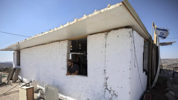 An Israeli settler looks out of a window at the outpost of Eviatar near the northern West Bank town of Nablus, Monday, June 21, 2021. Settlers established the outpost last month and say it is now home to dozens of families. Palestinians say it is built on private land and fear it will grow and merge with other large settlements nearby. (AP Photo/Sebastian Scheiner)