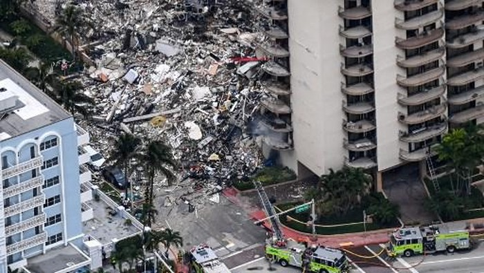 This aerial view, shows search and rescue personnel working on site after the partial collapse of the Champlain Towers South in Surfside, north of Miami Beach, on June 24, 2021. - The multi-story apartment block in Florida partially collapsed early June 24, sparking a major emergency response. Surfside Mayor Charles Burkett told NBCs Today show: My police chief has told me that we transported two people to the hospital this morning at least and one has died. We treated ten people on the site. (Photo by CHANDAN KHANNA / AFP)