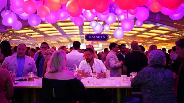 Pengunjung menikmati suasana pembukaan tempat kasino baru, Resorts World Las Vegas (24/6). Pemandangan kerumunan tanpa masker sangat kontras dengan masa pandemi global.