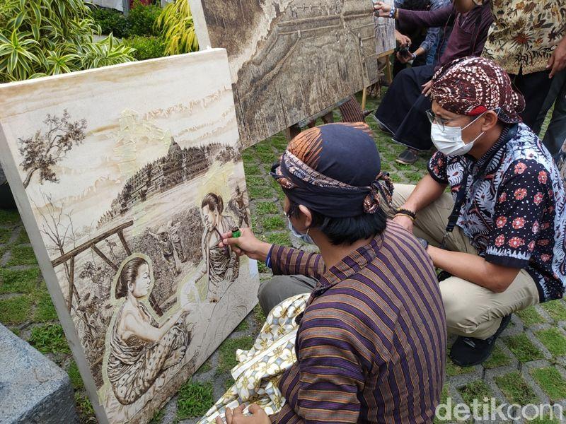 Wawan Geni saat menyelesaikan lukisan dengan pewarnaan obat nyamuk bakar