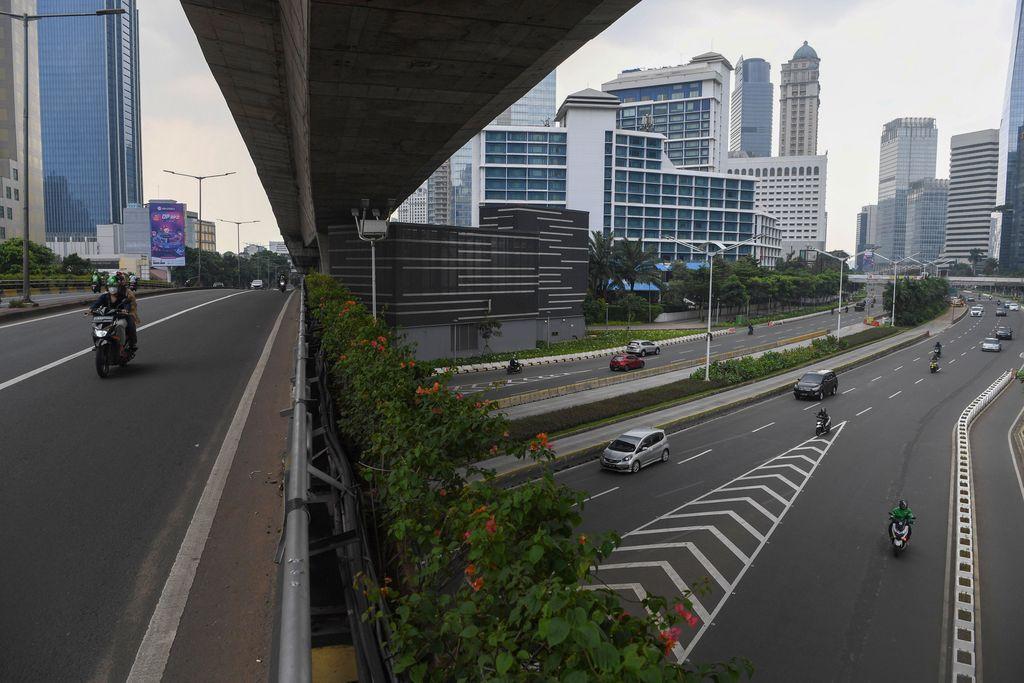 Pengendara melintasi kawasan jalan Sudirman yang lengang di Jakarta, Minggu (27/6/2021). Pembatasan kegiatan oleh pemerintah melalui PPKM Mikro hingga 5 Juli 2021 antara lain penutupan ruang publik, pembatasan operasional transportasi serta  penerapan protokol lebih ketat diharapkan dapat mengurangi penyebaran COVID-19 dimana fasilitas kesehatan telah penuh dalam menghadapi lonjakan pasien terkonfirmasi COVID-19. ANTARA FOTO/Wahyu Putro A/aww.
