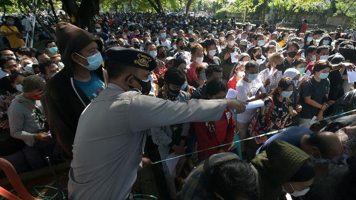 Anggota Polisi mengarahkan ribuan warga yang antre vaksinasi COVID-19 massal di Denpasar, Bali, Sabtu (26/6/2021). Petugas Kepolisian berupaya menertibkan masyarakat yang membludak saat mengikuti vaksinasi massal yang digelar di ruang publik tersebut untuk mencegah kerumunan dan agar tetap menerapkan protokol kesehatan COVID-19. ANTARA FOTO/Nyoman Hendra Wibowo/rwa.