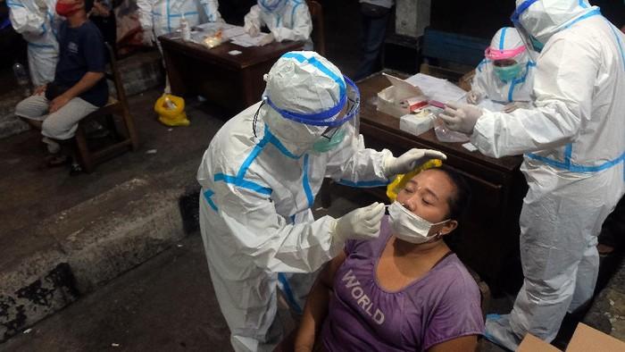 Petugas kesehatan mengambil sampel tes cepat Antigen dari sejumlah pedagang saat pelacakan COVID-19 di Pasar Kreneng, Denpasar, Bali, Rabu (23/6/2021). Pemerintah Kota Denpasar gencar menggelar tes cepat Antigen di tempat-tempat yang berpotensi menimbulkan kerumunan untuk menekan penularan COVID-19 saat situasi kasus positif meningkat sejak seminggu terakhir di wilayah itu. ANTARA FOTO/Nyoman Hendra Wibowo/rwa.