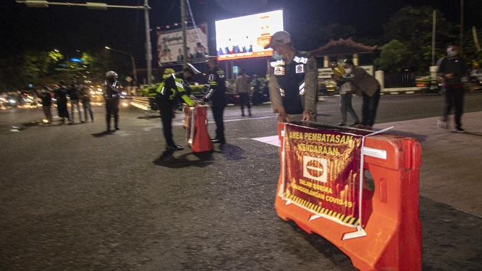 Petugas gabungan dari Polrestabes Palembang, Pol PP dan Dishub menyusun pembatas saat akan menutup jalan dalam rangka pembatasan mobilitas warga guna menekan penyebaran COVID-19 di Jalan POM IX, Palembang, Sumatera Selatan, Rabu (23/6/2021). Pembatasan tersebut dilakukan mulai pukul 21.00 WIB hingga 00.00 WIB di delapan titik persimpangan di Kota Palembang. ANTARA FOTO/Nova Wahyudi/rwa.