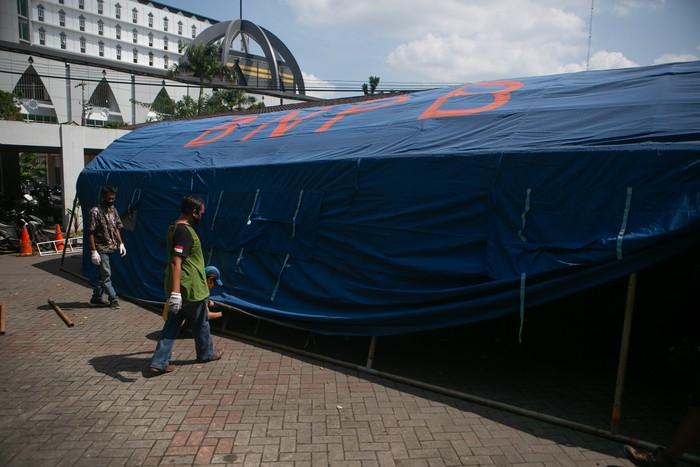 Relawan membangun tenda barak di Rumah Sakit Umum Pusat Dr. Sardjito, Sleman, DI Yogyakarta, Minggu (27/6/2021). Pembangunan tenda barak tersebut untuk melakukan screening dan penampungan sementara pengunjung di Instalasi Gawat Darurat (IGD) agar tidak terjadi kerumunan serta  mengantisipasi penularan COVID-19. ANTARA FOTO/Hendra Nurdiyansyah/foc.