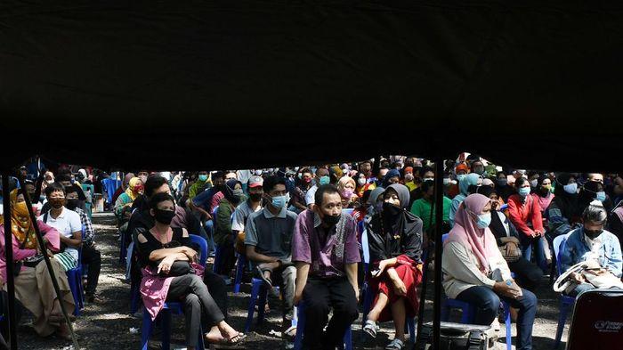 Warga antre untuk mendapatkan suntikan vaksin COVID-19 saat Vaksinasi Massal COVID-19 dalam rangka HUT ke-75 Bhayangkara di Kota Madiun, Jawa Timur, Sabtu (26/6/2021). Sebanyak 3.000 warga dari tiga kecamatan di Kota Madiun mengikuti vaksinasi dalam upaya penanganan pandemi COVID-19. ANTARA FOTO/Siswowidodo/rwa.