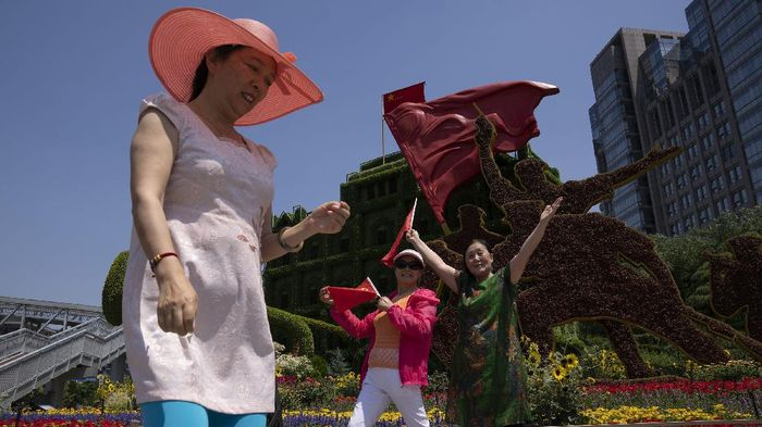 Residents pose for photos in front of a floral decoration for the upcoming 100th anniversary of the founding of Chinas ruling Communist Party in Beijing Tuesday, June 22, 2021. (AP Photo/Ng Han Guan)