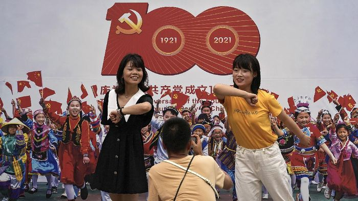Women gesture as they pose for a souvenir picture at a photo exhibition featuring peoples lives under communist party from 1921 to 2021 on display at the Wangfujing shopping district in Beijing, Monday, June 14, 2021. Authorities has started rehearsal in the capital city for an unspecified event to mark the 100th anniversary of the founding of Chinas ruling Communist Party, which will be observed on July 1. (AP Photo/Andy Wong)