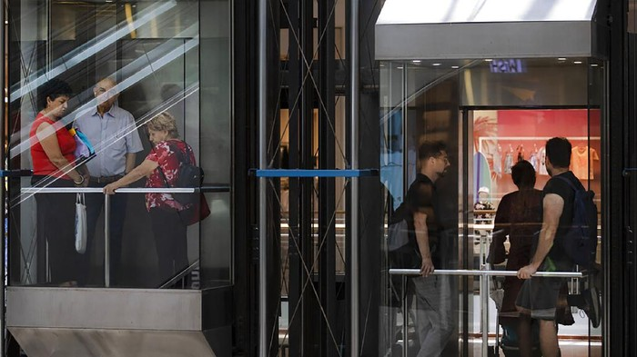 People ride an elevators at a shopping mall after restrictions requiring face masks indoors was lifted, in Tel Aviv, Tuesday, June 15, 2021. Israel lifted one of its last coronavirus restrictions Tuesday following a highly successful vaccination campaign. (AP Photo/Oded Balilty)