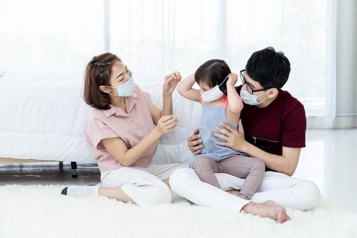 Keluarga mengenakan masker kesehatan.