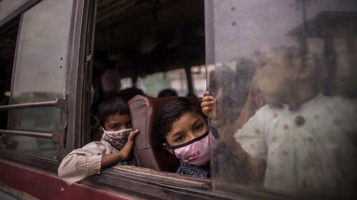 NEW DELHI, INDIA - APRIL 20: Children of migrant labourers working in Delhi look out the window of a bus as they head to their native villages after the Delhi government imposed a week long lockdown to battle the deadlier second wave of the Covid-19 coronavirus infections on on April 20, 2021 in New Delhi, India. Covid-19 cases are spiralling out of control in India, with daily infections approaching 300,000, according to health ministry data, bringing the nationwide tally of infections to almost 14 million. The latest wave has already overwhelmed hospitals and crematoriums. (Photo by Anindito Mukherjee/Getty Images)