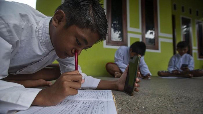 Tiga siswa menggunakan layanan panggilan video melalui telepon pintar dalam pembelajaran daring sekolah di Pulau Sabira, Kabupaten Kepulauan Seribu, DKI Jakarta, Jumat (18/6/2021). Kementerian Komunikasi dan Informatika (Kemenkominfo) menargetkan dapat membangun 9.113 BTS 4G hingga 2022 sehingga jaringan internet 4G dapat dihadirkan di 12.548 desa/kelurahan wilayah terdepan, terluar, dan tertinggal (3T), agar kesenjangan digital di Tanah Air dapat dipangkas. ANTARA FOTO/Aditya Pradana Putra/aww.