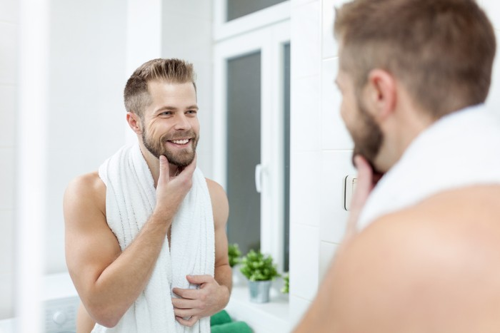 Morning hygiene, Handsome man in the bathroom looking in mirror