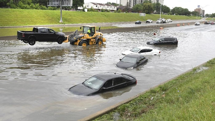A truck is hoisted from a flooded I75 and Canfield Street as heavy rain flooded streets in the metro area of Detroit, on Saturday, June 26, 2021. A state of emergency has been declared for Detroit and surrounding Wayne County following daylong rain that flooded freeways and streets. (Max Ortiz/Detroit News via AP)