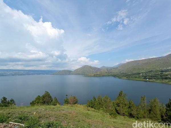 Latar Danau Toba yang sangat indah membuat wisatawan terkagum-kagum.