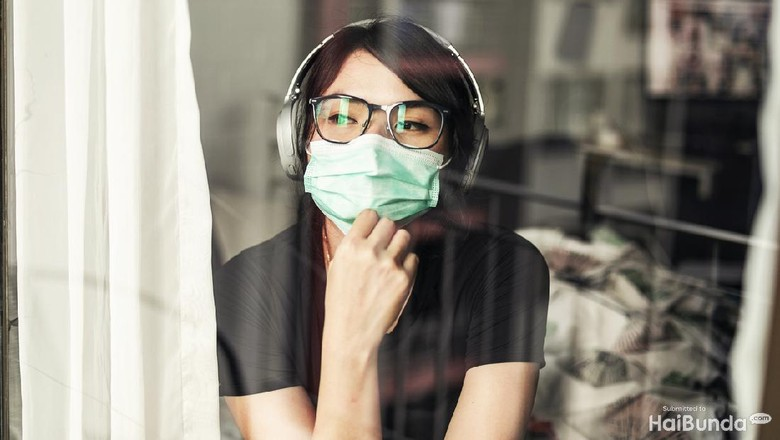 Portrait of young woman in the her apartment wearing face protective mask to prevent Coronavirus