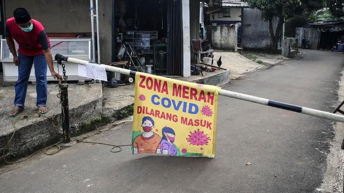 Warga menjaga pintu masuk ke pemukiman yang ditutup karena menjadi daerah zona merah penyebaran COVID-19 di Pamulang Barat, Tangerang Selatan, Banten, Rabu (23/6/2021). Lockdown lokal dilakukan karena sebanyak 17 warga di daerah itu terpapar COVID-19. ANTARA FOTO/Muhammad Iqbal/hp.