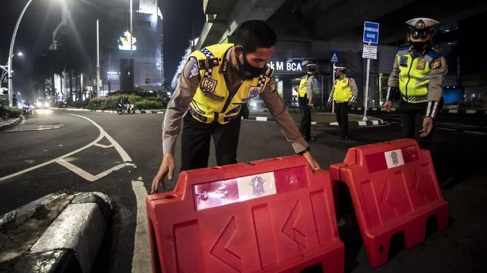 Petugas kepolisian menyusun pembatas jalan saat akan melakukan penutupan jalan dalam rangka pembatasan mobilitas warga guna menekan penyebaran COVID-19 di kawasan Bulungan, Jakarta, Senin (21/6/2021). Pembatasan tersebut dilakukan mulai pukul 21.00 WIB hingga 04.00 WIB di 10 titik di Kota Jakarta  diantaranya Jalan Cikini Raya, kawasan Jalan Sabang, kawasan BKT, kawasan Kemang, PIK 2, kawasan Kota Tua dan Bulungan. ANTARA FOTO/Muhammad Adimaja/wsj.