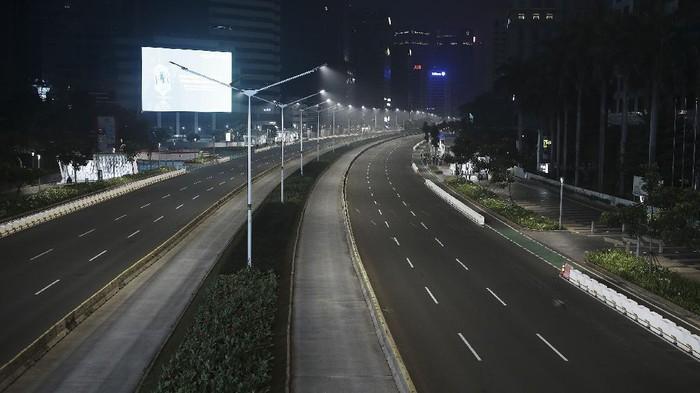 Suasana malam jalan yang terlihat sepi di  kawasan Sudirman, Jakarta, Rabu (12/5/2021) malam. Polda Metro Jaya memberlakukan crowd free night untuk mencegah kerumunan takbir keliling di malam Idul Fitri 1442 yang berlaku mulai pukul 22:00 malam ini  untuk mencegah penularan COVID-19.  ANTARA FOTO/ Reno Esnir/hp.
