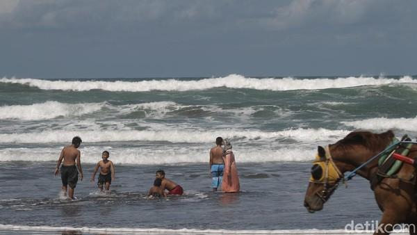 Para pengunjung pantai Parangtritis itu terlihat asyik bermain air di bibir pantai.