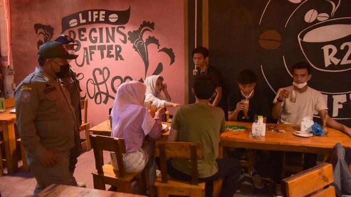 Petugas gabungan dari Kepolisian dan Satpol PP meminta pengunjung dan pemilik usaha kuliner yang melewati batas aturan waktu operasional untuk membubarkan diri saat sidak penerapan Pemberlakuan Pembatasan Kegiatan Masyarakat (PPKM) Mikro di Medan, Sumatera Utara, Jumat (30/6/2021) malam. Tim Patroli Protokol Kesehatan dan PPKM Mikro menyegel warung makan tersebut  akibat melanggar Surat Edaran (SE) Wali Kota Medan Bobby Nasution. ANTARA FOTO/Fransisco Carolio/Lmo/wsj.