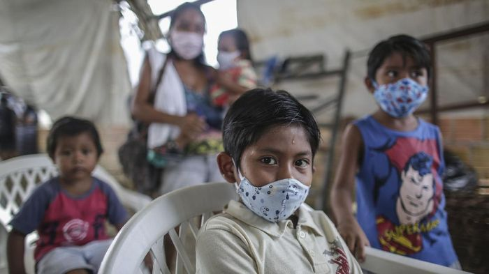 MANAUS, BRAZIL - MAY 21: Indigenous boys wearing protective masks wait for vaccine and testing at Parque das Tribos community, on May 21 2020 in Manaus, Brazil.  Medical teams from Healths Secretary of Manaus area performing vaccination against flu and testing to detect coronavirus (COVID-19) infections on indigenous communities. (Photo by Andre Coelho/Getty Images)