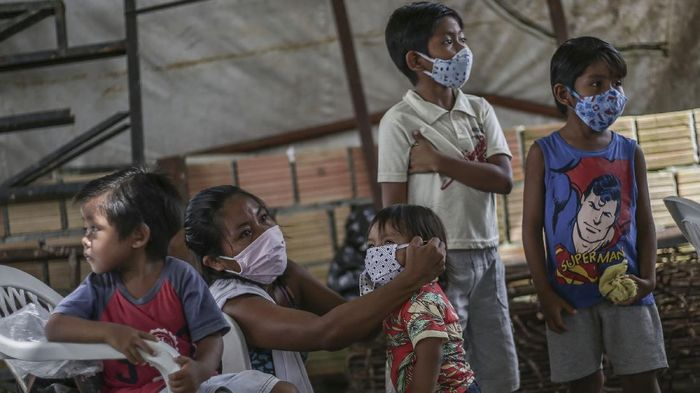 MANAUS, BRAZIL - MAY 21: An indigenous woman puts protective masks on her kids while waits for vaccine and testing at Parque das Tribos community, on May 21 2020 in Manaus, Brazil.  Medical teams from Healths Secretary of Manaus area performing vaccination against flu and testing to detect coronavirus (COVID-19) infections on indigenous communities. (Photo by Andre Coelho/Getty Images)