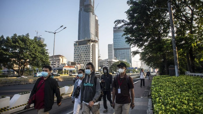 Sejumlah pekerja berjalan di jalur pedestrian Jalan Jenderal Sudirman, Jakarta, Jumat (2/7/2021). Pemerintah akan menerapkan PPKM Darurat di Pulau Jawa dan Bali mulai 3 Juli mendatang, salah satunya mewajibkan menerapkan