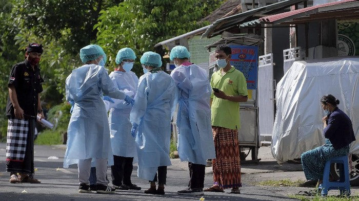 Petugas kesehatan mendata warga yang terpapar COVID-19 dan melakukan isolasi mandiri di Banjar Terunasari, Desa Dauh Puri Kaja, Denpasar, Bali, Kamis (1/7/2021). Satgas COVID-19 menerapkan PPKM Mikro secara ketat di kawasan tersebut menyusul 20 warga setempat dinyatakan positif COVID-19 setelah melakukan tes usap PCR yang diikuti 43 warga pada Selasa (29/6). ANTARA FOTO/Nyoman Hendra Wibowo/wsj.
