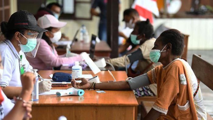 Petugas kesehatan menyuntikkan vaksin COVID-19 kepada warga di Agats, Asmat, Papua, Kamis (1/7/2021). Vaksinasi yang digelar dalam rangka HUT Bhayangkara ke-75 tersebut diperuntukkan bagi warga Agats sebagai upaya guna mempercepat program pemerintah untuk mencapai kekebalan komunal menuju Indonesia sehat bebas COVID-19.ANTARA FOTO/Puspa Perwitasari/aww.