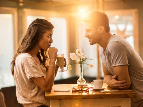 Young woman drinking coffee and communicating with her smiling boyfriend in a cafe.