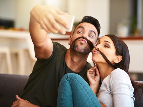 Shot of a young couple taking selfies together at home