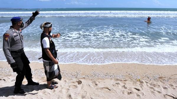 Polisi bersama Pecalang atau petugas keamanan adat Bali meminta wisatawan untuk meninggalkan kawasan wisata Pantai Kuta.