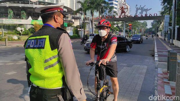 Polisi jalau pesepeda di Jl Jend Sudirman, Senayan, Jakarta, saat PPKM Darurat, 3 Juli 2021. (Azhar Bagas Ramadhan/detikcom)