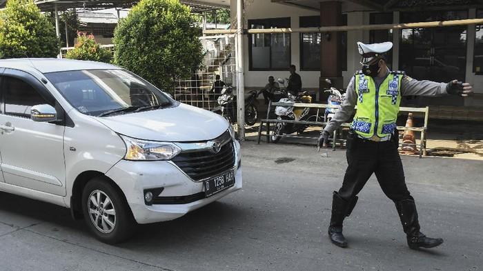Petugas Kepolisian memberhentikan kendaraan yang berplat nomor luar Jabodetabek di Kalimalang, Jakarta Timur, Sabtu (3/7/2021). Pada Pemberlakuan Pembatasan Kegiatan Masyarakat (PPKM) Darurat petugas melakukan penyekatan kendaraan berplat daerah dan memeriksa identitas penumpang guna mencegah penyebaran wabah COVID-19. ANTARA FOTO/ Fakhri Hermansyah/hp.