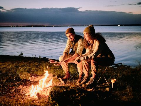 Positive young couple sitting at lake shore and making sausages on fire during night camping