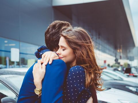Loving young couple say good bye at airport, man and woman embracing at car parking lot.