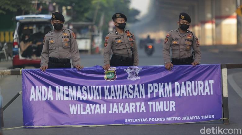Sejumlah petugas memeriksa pengendara motor dan mobil di pos penyekatan Kalimalang, Jakarta. Pemeriksaan dilakukan sebagai bagian dari penerapan PPKM Darurat.
