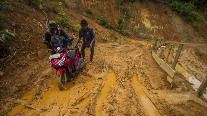 Jalan penghubung antar desa di Kalimantan Selatan, rusak akibat longsor pascabanjir. Kondisi jalan yang belum diperbaiki membuat warga sulit beraktivitas.