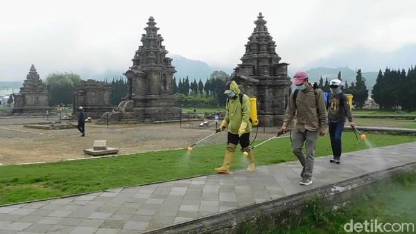 Sejumlah petugas sedang melakukan penyemprotan disinfektan di area komplek Candi Arjuna, Banjarnegara, Jawa Tengah, Minggu (4/7/2021).