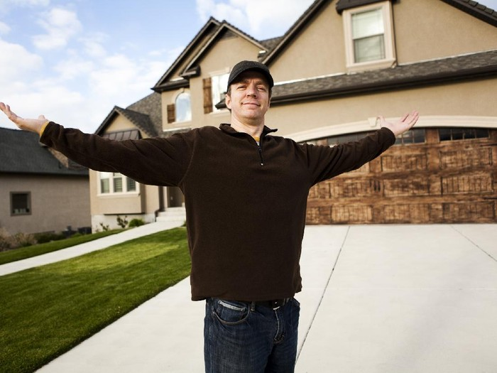 Man standing in front of his new home.
