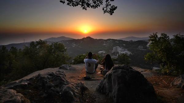 Pasangan muda tengah menikmati lansekap matahari terbenam saat mendaki di Desa Chahtoul.