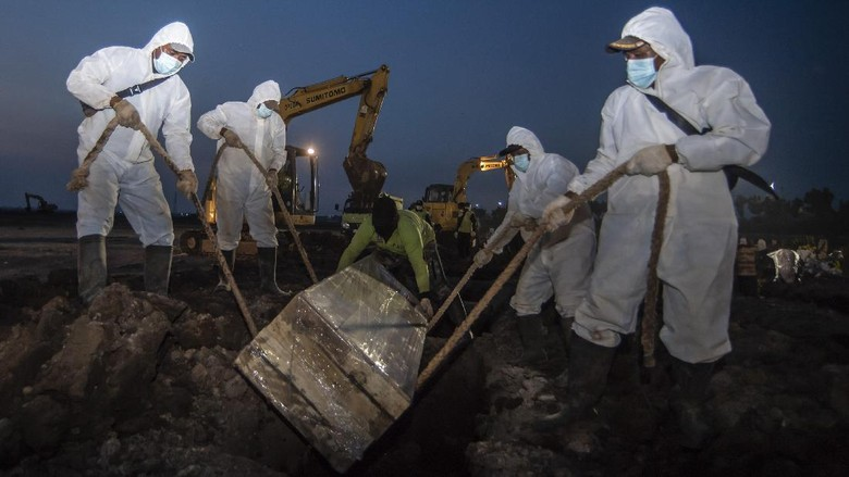 Petugas memakamkan jenazah dengan protokol COVID-19 di TPU Rorotan, Cilincing, Jakarta, Minggu (4/7/2021). Jumlah kematian akibat COVID-19 per hari Minggu (4/7/2021) mencapai 555 kasus, yang menjadi rekor tertinggi sejak kasus pertama COVID-19 di Indonesia diumumkan Presiden Joko Widodo pada awal Maret 2020.  ANTARA FOTO/Muhammad Adimaja/aww.
