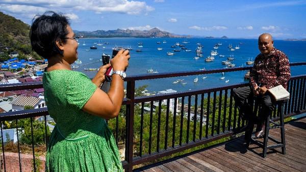 Wisatawan tengah mengabadikan momen dengan latar belakang lansekap yang indah.