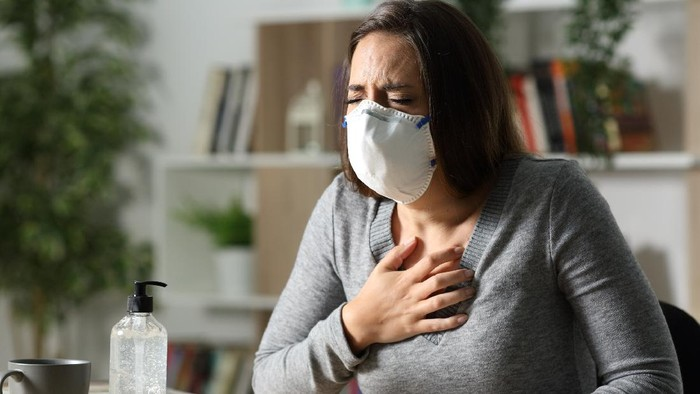 Woman with protective mask suffocating due coronavirus holding chest sitting on a desk at nigh at home