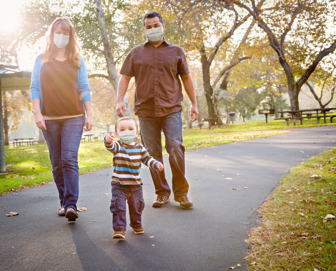 A happy family wear face masks while walking in their neighborhood during the COVID-19 pandemic.