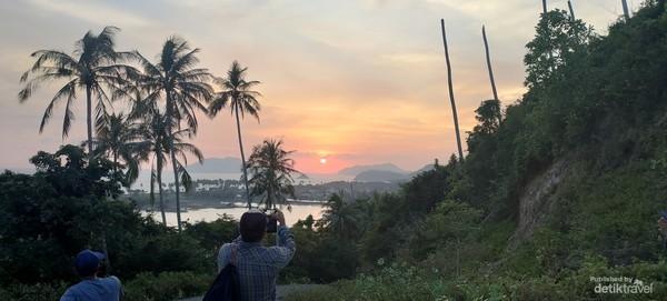 Seorang wisatawan luar negeri sedang menikmati matahari terbenam disalah satu sudut pulau.
